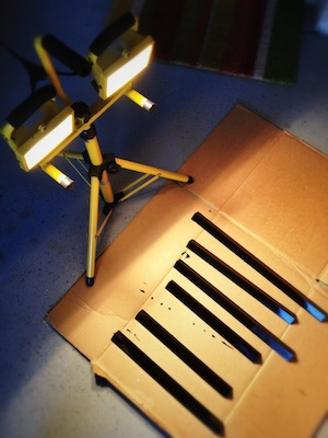 Drying the finished spray painted rack pieces under halogen work lamps
